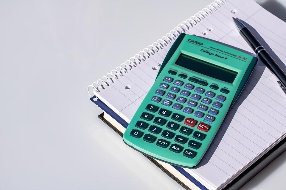 calculatrice posée sur cahier avec stylo